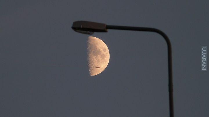 Latarnia & 'Tranzyt' samolotu na tle tarczy Księżyca