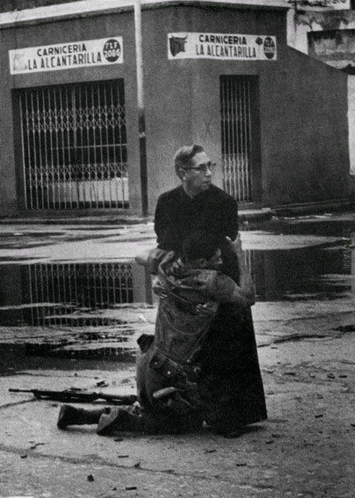 Umierający żołnierz ściskający księdza po tym, jak został trafiony pociskiem snajperskim.
